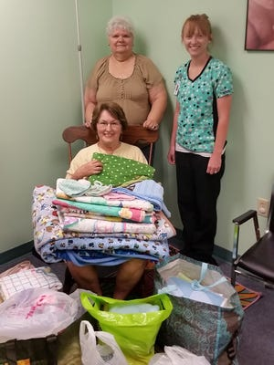 The Shawneetown United Daughters of the Confederacy Chapter 2706 recently donated 65 handmade blankets, quilts and caps to the Marion County Health Clinic in Yellville. Shown are Virginia Griffin and Betty Morrow of the Shawneetown Chapter and Traci Holmes of the clinic.