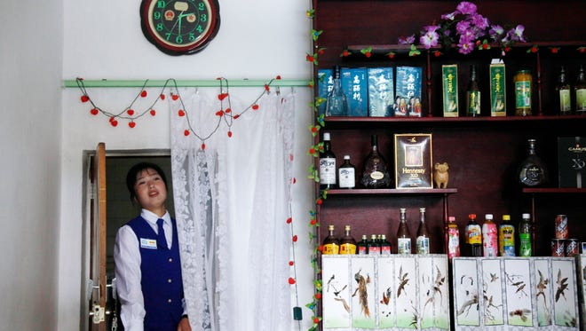 """In this Aug. 29, 2011, photo, a North Korean waitress walks through a door under a clock with Chinese emblems at a restaurant in Rason city in North Korea. North Korea said Friday, Aug. 7, 2015, that it will establish its own time zone next week by pulling back its current standard time by 30 minutes. Local time in North and South Korea and Japan is the same — nine hours ahead of GMT. It was set during Japan's rule over what was single Korea from 1910 to 1945. The establishment of """"Pyongyang time"""" is meant to root out the legacy of the Japanese colonial period, the North's official Korean Central News Agency said. (AP Photo/Ng Han Guan, File)"""