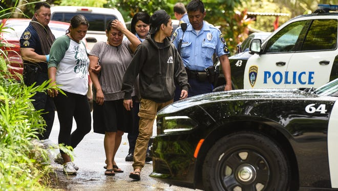 A woman can be seen overcome with emotion as she and others are led away from a area where Guam Police Department personnel are conducting a death investigation at a residence along Chalan Koda in Dededo on Saturday, June 16, 2018. Limited information is available until an autopsy, schedule to be done later this week, is performed by the island's chief medical examiner, said Sgt. Paul Tapao, GPD spokeman.