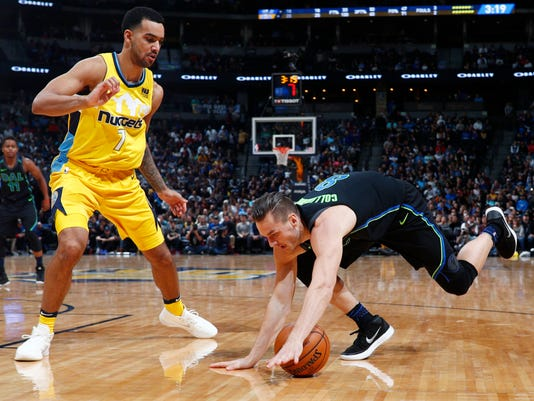 Dallas Mavericks guard Kyle Collinsworth, right, falls on a drive as Denver Nuggets forward Trey Lyles watches during the first half of an NBA basketball game Saturday, Jan. 27, 2018, in Denver. (AP Photo/David Zalubowski)