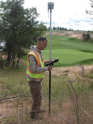 Nate Jahn, Mid-State Technical College Civil Engineering student, records topographical data from a natural area surrounding a green at Sand Valley.