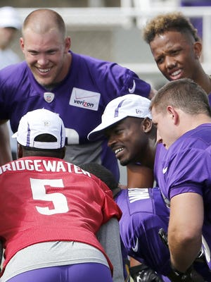 Minnesota Vikings players, clockwise from top left, Kyle Rudolph, Charles Johnson, Zach Line and Adrian Peterson listen as quarterback Teddy Bridgewater (5) calls a play during practice at training camp Sunday.