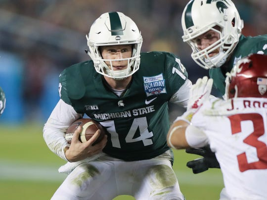 Michigan State quarterback Brian Lewerke runs during