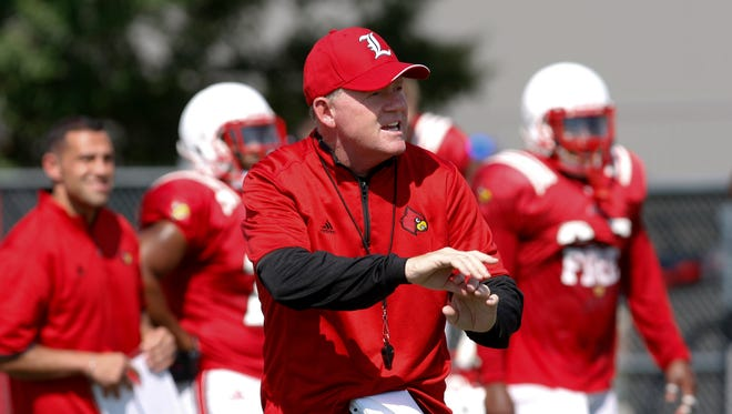 U of L Head Coach Bobby Petrino gives instructions during practice at the Papa John's Cardinal Stadium practice field.   Aug.11, 2015