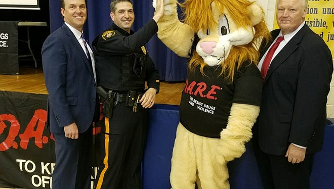 Celebrating the graduation of 110 fourth-graders from the revived DARE program at Roosevelt School are Somerset County Prosecutor Michael Robertson, Manville Police Det. David Sheffrin, who taught the course, Daren, the course's mascot, and Manville Police Chief Mark Peltack.