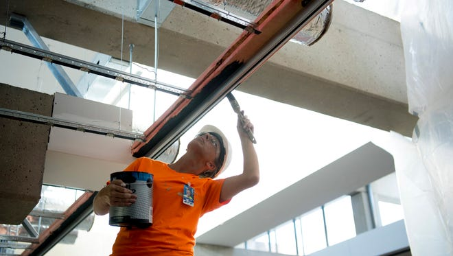Heather Hurt with Owen Simms Painting primes the wooden frame for the drop ceilings at the Evansville Regional Airport Friday morning. Renovations at the airport are expected to be finished in October.