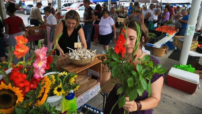 Nikki Cooper, who grew up in New Albany, says she's encouraged by the change in the downtown area over the past few years. Saturdays are busy at the year-round Farmer's Market, where she sells vegetables as well as floral bouquets from the flowers she grows at her and her husband's Lost Acres Farm in Ramsey, Ind.
