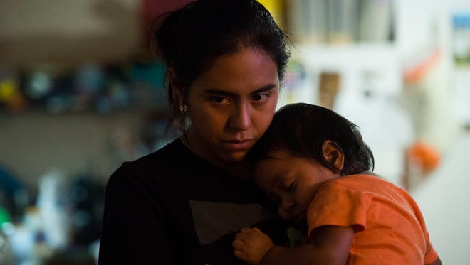 Yahel Salazar holds her son Moises Ramirez in their Rutledge, Tenn., home June 26, 2018. Salazar's husband, Cristino Ramirez, was detained by U.S. Immigration and Customs Enforcement agents when they raided the Southeastern Provision meat-packing plant where he worked outside Bean Station.