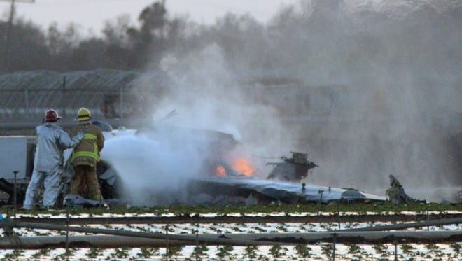 Firefighters extinguish the remaining flames of a military airplane that crashed in a field near Naval Station Ventura County near Port Hueneme, Calif., killing the pilot Wednesday, Oct. 29, 2014.