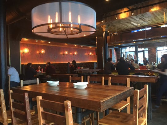 Simple wood tables and chairs contrast modern lighting