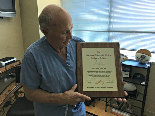Dr. O. Tom Johns displays a national award he won in