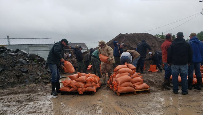Augusta residents fill sandbags at the country shop as flood water invades the town Tuesday.