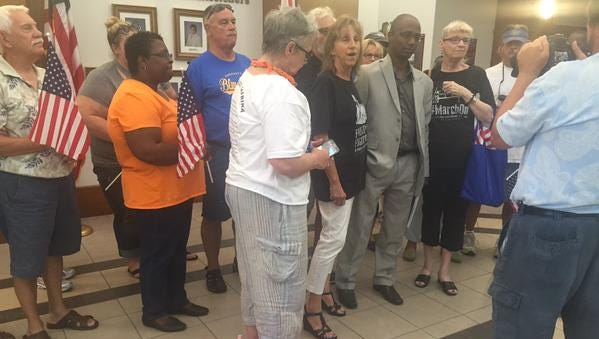 Commissioner Lumon May tells flag protesters county will take down confederate flags.