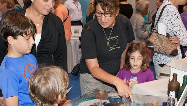 People enjoy displays at the North American Seaglass Festival. This year's event happens Aug. 26-26, 2016.