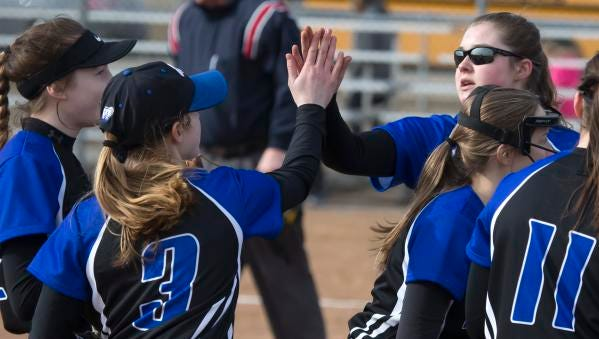 Annika Johnson and Neva Oates slap hands as the Oshkosh West players make their way back to the dugout Thursday at Oshkosh West High School on March 29, 2018 in Oshkosh, Wisc.