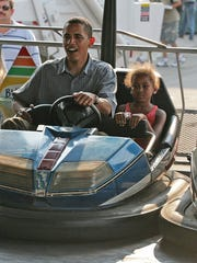From Aug. 16, 2007: Then-U.S. Sen. and Democratic presidential candidate Barack Obama and his youngest daughter, Sasha, driving a bumper car together while Michelle Obama, left, and their oldest daughter, Malia, right, drive their own cars at the Iowa State Fair.