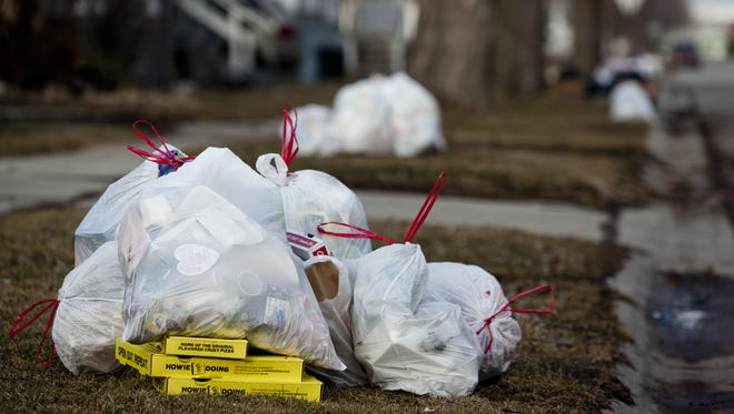 Bags of garbage sit at a curb.