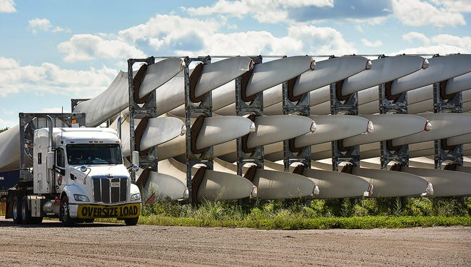 Large windmill blades and components sit in a train yard Tuesday, Aug. 22, along Minnesota Highway 23 in Rockville. The lot serves as a hub for Minnesota wind projects.