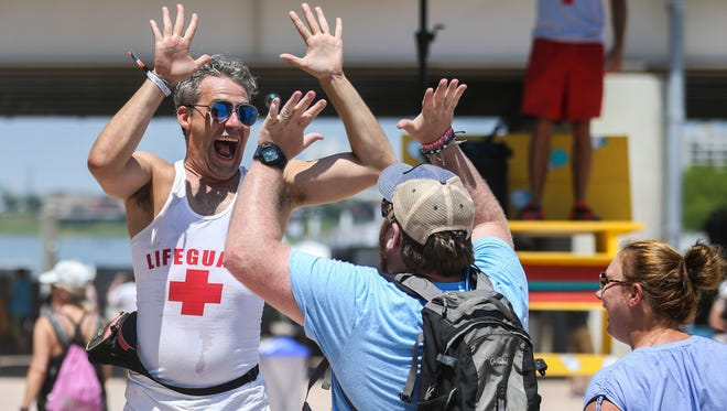 Greeting Forecastle Festival attendees with high fives, smiles and bubbles are the Lifeguards, a tradition at the three-day event.