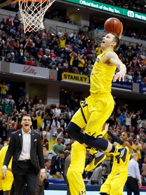 Michigan Wolverines guard Nik Stauskas (11) dunks the ball after the game to celebrate defeating the Ohio State Buckeyes.