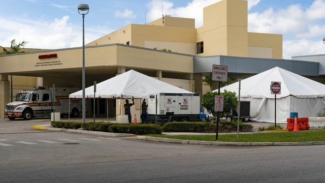 Workers set up a second tent outside the ER that will eventually be used to screen patients at Boca Raton Regional Hospital in Boca Raton, Florida on  March 18, 2020.