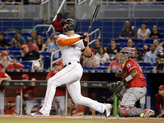 Miami Marlins' Giancarlo Stanton, left, watches after hitting a two-run home run as Los Angeles Angels catcher Martin Maldonado looks on during the first inning of an interleague baseball game, Friday, May 26, 2017, in Miami. (AP Photo/Lynne Sladky)