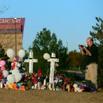 "Aurora city employee Demetrius Romo-Gilmore takes a photograph of a makeshift memorial to the 12 movie theater shooting victims built across the street from the Century 16 Theater on July 24, 2012, in Aurora, Colo. A lawsuit, filed Tuesday, Sept. 16, 2014, is aimed at forcing Internet-based suppliers of guns, ammunition and military equipment to take ""reasonable steps"" before completing sales."
