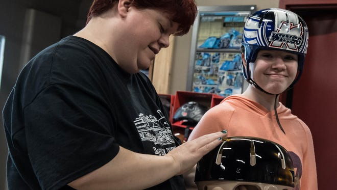 """Battle Creek residents Vicki Kopf and her daughter, 15-year-old Abigail """"Abbie"""" Kopf, look at a custom Batman helmet Tuesday created for her by Springfield-based motorcycle shop Hot Rods and Handlebars. Abigail Kopf is one of two survivors from a random shooting spree Feb. 20 in Kalamazoo County."""