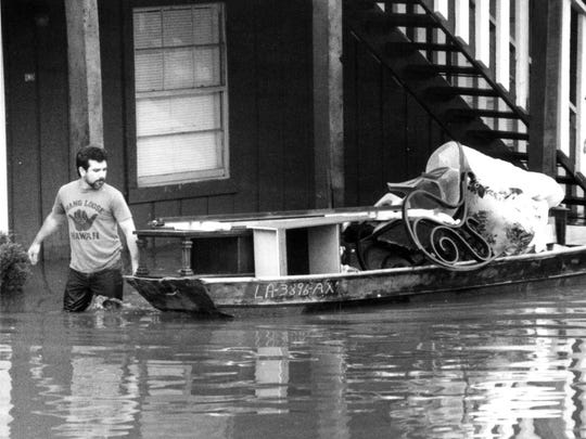 Jessie Garcia, left, and Tony Napier walked a boat filled with household items out of the Westwood Townhouses' parking lot on Glenwood Drive in West Monroe in April 1991.