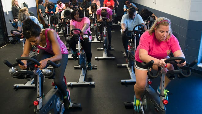 Phelicia Bush, left, rides bikes with other participants during the Get Fit 2015 fitness class at the Bell Road YMCA on Tuesday, Jan. 20, 2015.