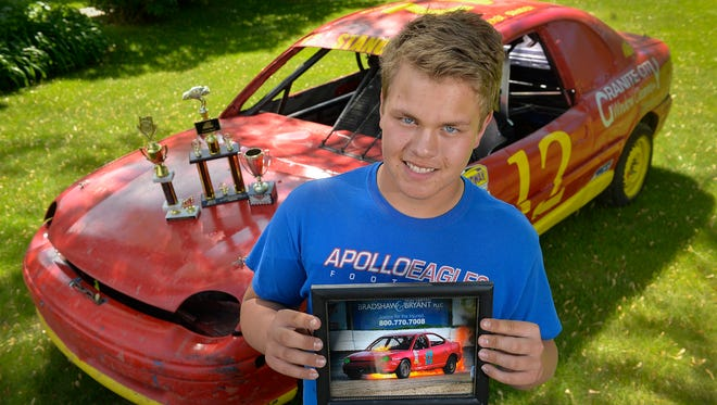 Derek Stanoch, 14, St. Cloud, holds a photo of his first race car that caught fire after it rolled. He was only 13 then. Only a year later, he is enjoying some success racing his 1995 Dodge Neon on area dirt tracks in the IMCA Sport Compacts and Hornets classes.