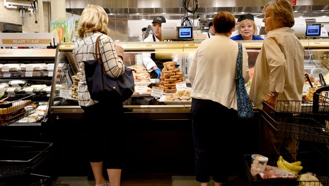 Wegmans employees Kelly Roldan, left, and Nilva Levin help customers with prepared foods, shortly after the opening of the Montvale store on Sunday.