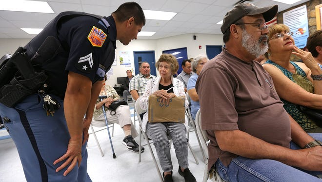 Police Area Representative Officer Eric Castaneda of the Central Regional Command Center talks with Corbin/Sambrano Neighborhood Association President Shirley Neagle during their meeting July 24 at the Seville Recreation Center. The recreation center was the site of an altercation between a group of teens, a mother and police.