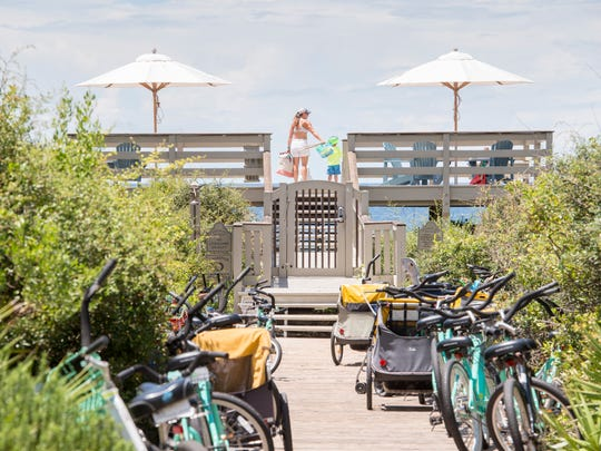 Beachgoers make their way through a private gated walkover at Rosemary Beach in Walton County, Florida on Wednesday, July 19, 2017.