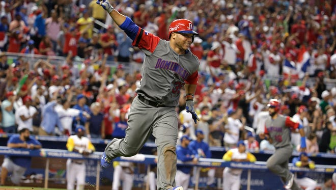 Dominican Republic's Welington Castillo celebrates after hitting a RBI single to score the go ahead run in the eleventh inning.