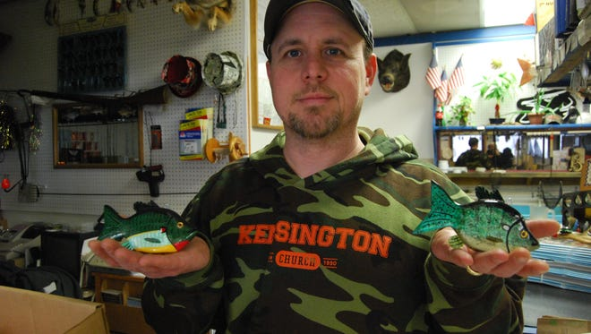 Brian King, of Brian's Blue Water Bait in Ira Township holds ice fishing decoys crafted by Chuck Meldrum