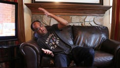 In the living room of his New Milford home, Tahir Qureshi