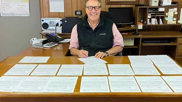 Summerfield Township Supervisor John Chandler signs 17 road improvement project contracts. They are slated to be completed this upcoming spring.