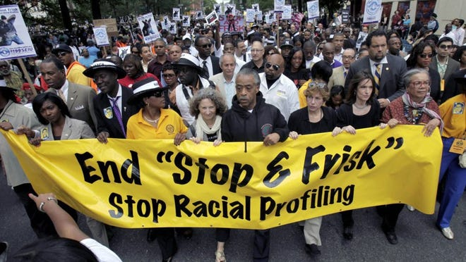 FILE — In this June 17, 2012, file photo, the Rev. Al Sharpton, center, walks with demonstrators during a silent march to end New York's 'stop-and-frisk' program. On Aug. 12, 2013, a federal judge sitting in New York said the department made thousands of racially discriminatory street stops and appointed a monitor to direct changes. (AP Photo/Seth Wenig, File)