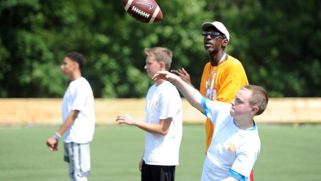 Mark Foust, 12, right, passes a football under the watch of former Tennessee quarterback Tony Robinson during the sixth annual Camp 76, featuring former University of Tennessee and NFL players at Johnny Long Training Academy on Saturday, June 4, 2016.