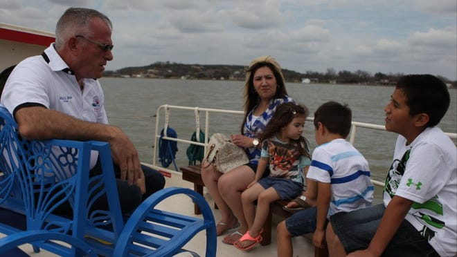 Michelle Gaitan/Standard-Times Captain Mack Fox of the Tule Princess shares a little bit of Lake Nasworthy his with a family as they check out the view.