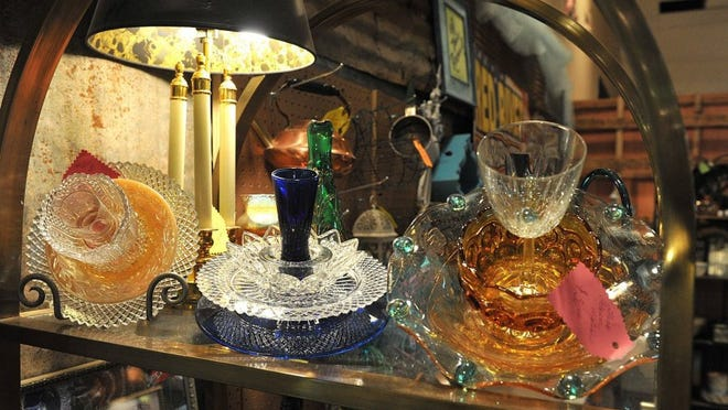 TORIN HALSEY/TIMES RECORD NEWS An array of vintage colored glass collectibles is on display at the Alley Cat Vintage Mercantile downtown on Indiana Street. The business began in Archer City in 2000 and eventually moved to Wichita Falls. The owners and more than 100 vendors offer everything from rare books to handcrafted art and fine furniture to rustic implements.