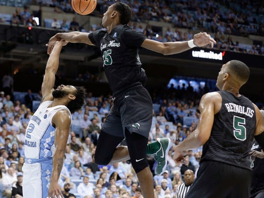 North Carolina's Joel Berry II (2) drives to the basket while Tulane's Melvin Frazier (35) and Cameron Reynolds (5) defend during the first half of an NCAA college basketball game in Chapel Hill, N.C., Sunday, Dec. 3, 2017. (AP Photo/Gerry Broome)