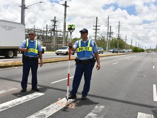 In this file photo Guam Police Department Highway Patrol Division officers at the scene of an auto-bicycle crash. Eric Bell. Bell died two weeks after he was struck by a car while walking his bike across Route 1 at a crosswalk, police said.