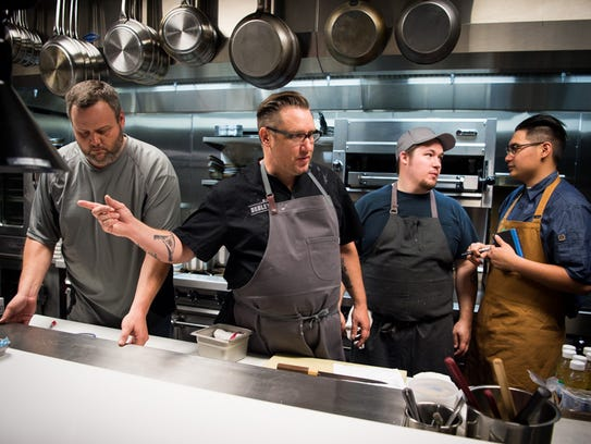 Chef RJ Cooper, center, works with staff in the kitchen