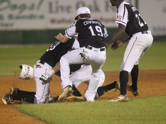 Madison County's Dustin Bass is smothered by teammates and his helmet knocked off after hitting a game-winning single in the bottom of the eighth inning during a Region 3-1A final at Suwannee High in Live Oak.