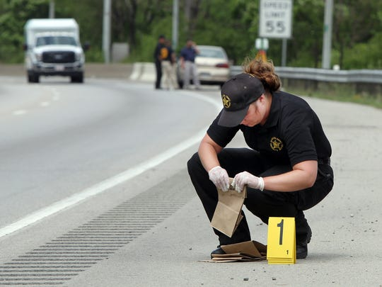 Hamilton County Sheriff's Department evidence technician Heather Sanderson collects evidence and evidence markers along the shoulder of northbound I-75 near Davis Street.