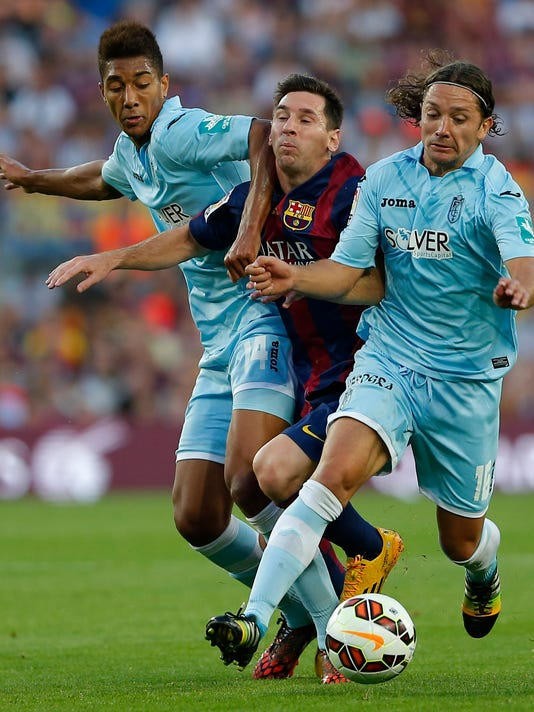 Barcelona's Lionel Messi from Argentina is tackled by Granada's Eddy Silvestre, left, and Manuel Iturra during a Spanish La Liga soccer match between F.C. Barcelona and Granada C.F. at the Camp Nou stadium in Barcelona, Spain, Saturday, Sept. 27, 2014. (AP Photo/Emilio Morenatti)
