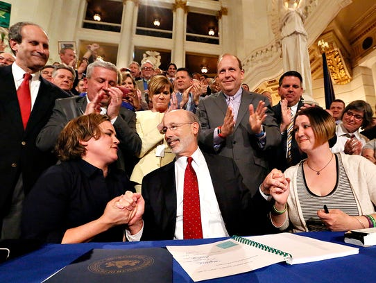 Gov. Tom Wolf, center, flanked by Lolly Bentch, left,