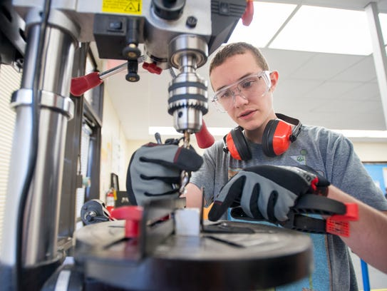 Jonah Thrasher, 16, works on a drill press during manufacturing